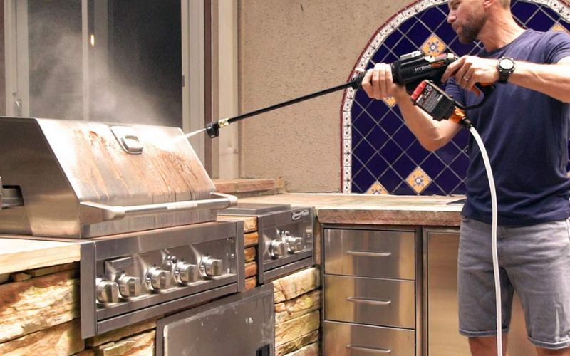 man cleaning grill with worx hydroshot cleaner